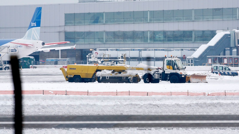 A snow plough drives past an airplane parked at Heathrow Airport in west London, Sunday, Dec. 19, 2010. (AP / Akira Suemori)
