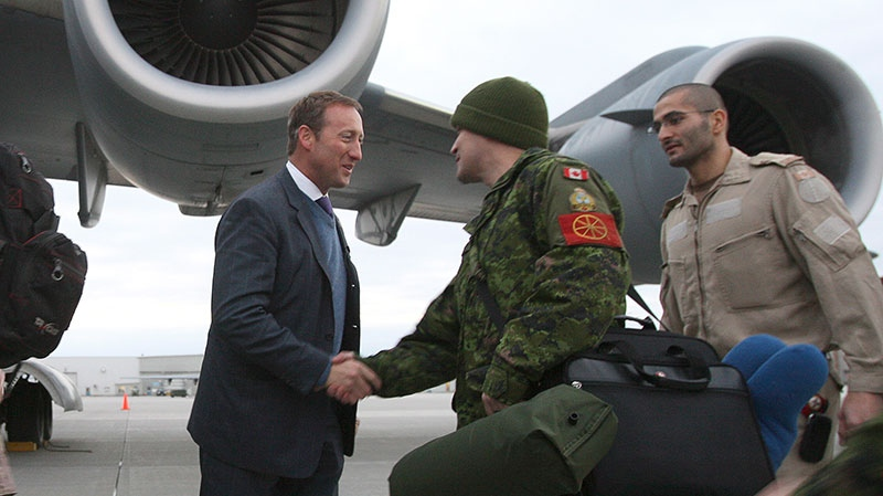 Minister of Defence Peter MacKay shakes hands with Canadian forces members of Squadron 429 at CFB Trenton, on Tuesday Jan. 15, 2013. (Lars Hagberg / THE CANADIAN PRESS)