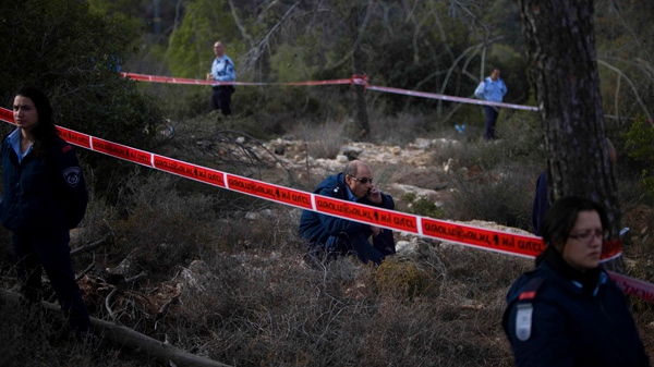 Israeli police stand guard near the body of U.S. tourist Christine Logan, not seen, after she was found in a wooded area near the village of Mata, outside Jerusalem, Sunday, Dec. 19, 2010. (AP / Tara Todras-Whitehill)