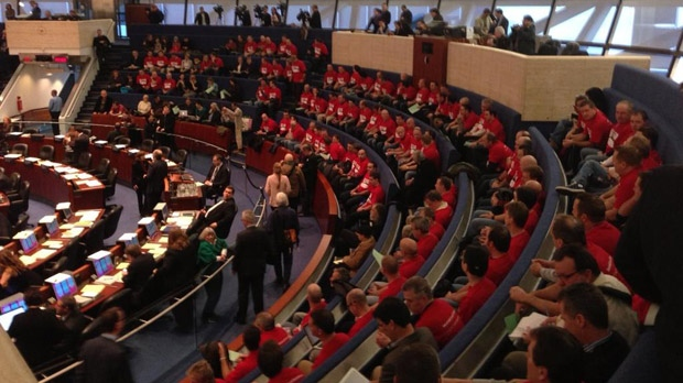 Toronto firefighters, dressed in red T-shirts, hold a visual protest as city council debates the proposed 2013 budget on Tuesday, Jan. 15, 2013. (Katie Simpson/CP24)