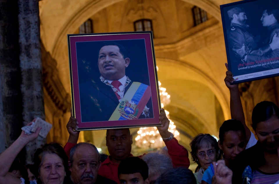 A man holding a framed image of Venezuela's President Hugo Chavez leaves a cathedral after attending a Mass to pray for the recovery of Chavez, in Havana, Cuba, Saturday, Jan. 12, 2013. (AP / Ramon Espinosa)