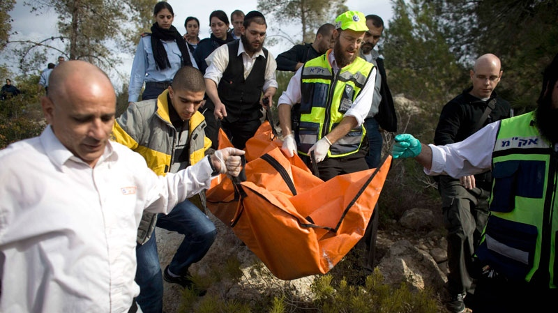Israeli rescue workers carry the body of U.S. tourist Christine Logan after she was found in a wooded area near the village of Mata, outside Jerusalem, Sunday, Dec. 19, 2010. (AP / Tara Todras-Whitehill)