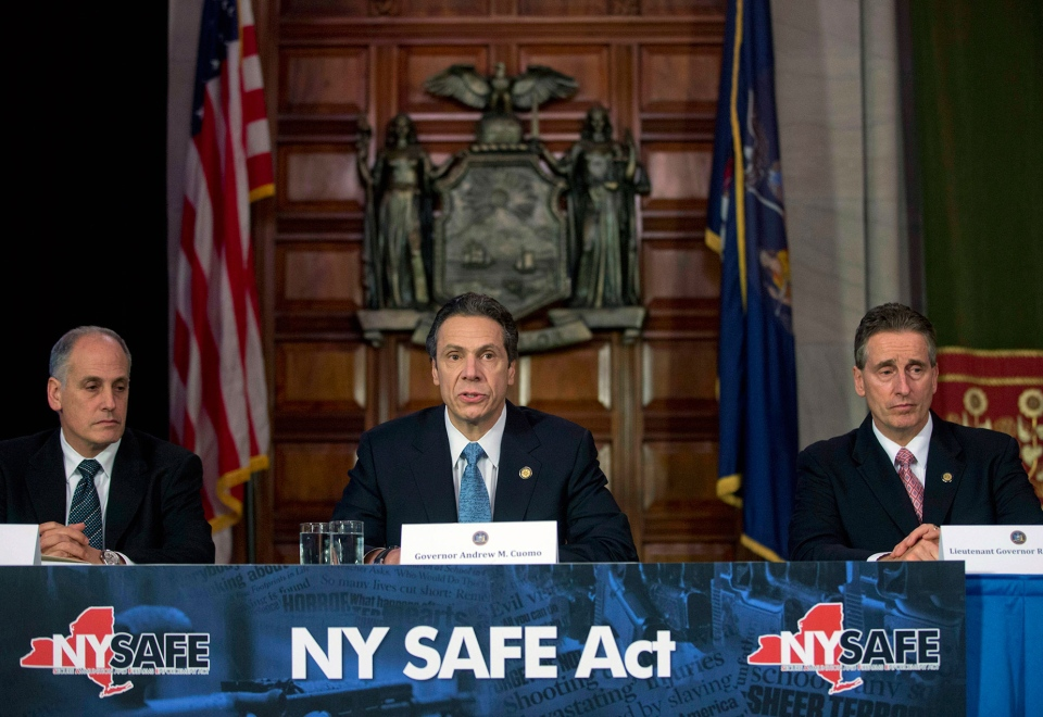 New York Gov. Andrew Cuomo, centre, speaks during a news conference announcing an agreement with legislative leaders on New York's Secure Ammunition and Firearms Enforcement Act in the Red Room at the Capitol in Albany, N.Y. on Monday, Jan. 14, 2013. (AP / Mike Groll)