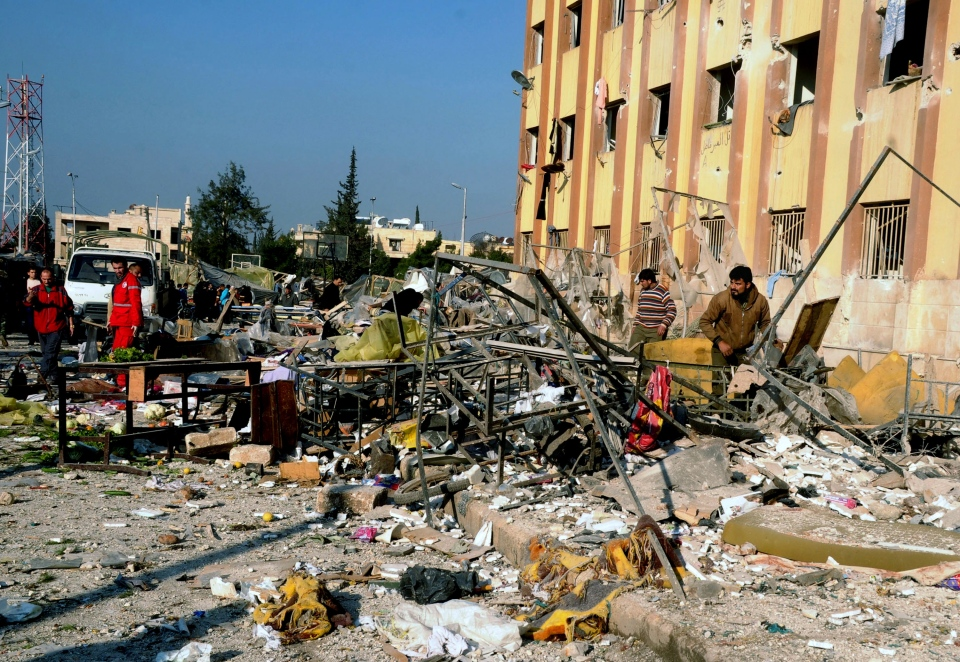 Syrian people gather at the site after an explosion hit a university in Aleppo, Syria, Tuesday, Jan. 15, 2013. (SANA)