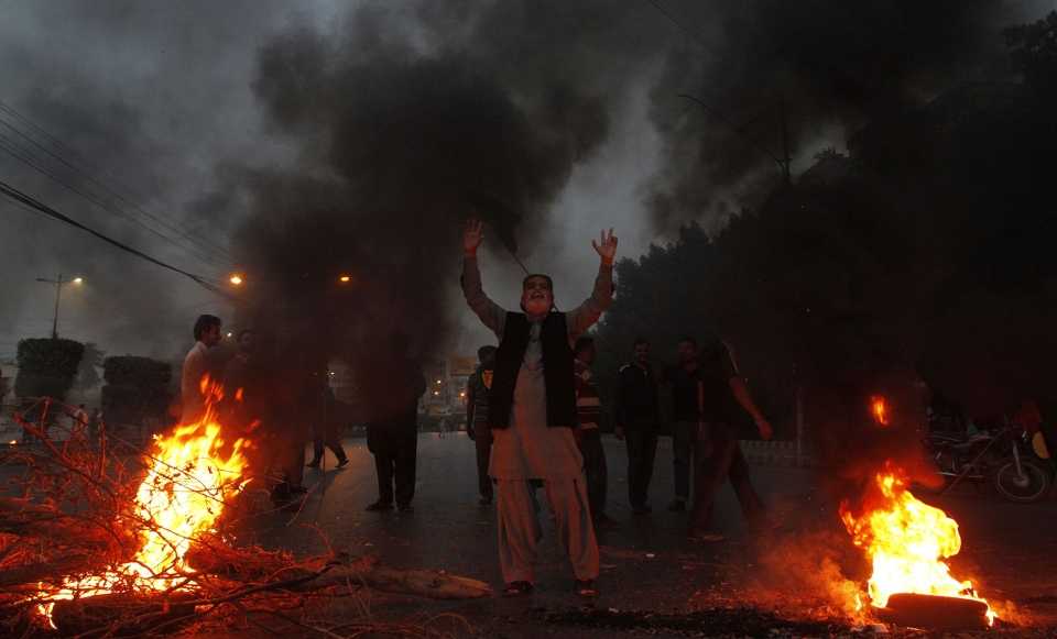 Supporters of Pakistan's ruling People's party burn tires to condemn a Supreme Court's order to arrest Prime Minister Raja Pervez Ashraf, in Karachi, Pakistan on Tuesday, Jan. 15, 2013. (AP / Shakil Adil)