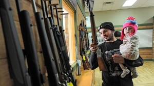 In this undated file photo, a man handles a rifle while holding his 11-month-old daughter at Highsmith Guns in Greenfield. (AP Photo / Daily Reporter / Tom Russo)