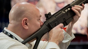 A convention attendee looks through the sight of a Sig Sauer semiautomatic rifle at the 35th annual SHOT Show in Las Vegas, Tuesday, Jan. 15, 2013. (AP / Julie Jacobson)