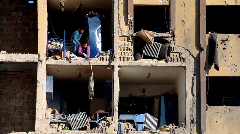 Syrians stand in rubble of the damaged university building caused by an explosion in Aleppo, Syria, Tuesday, Jan. 15, 2013. (SANA)