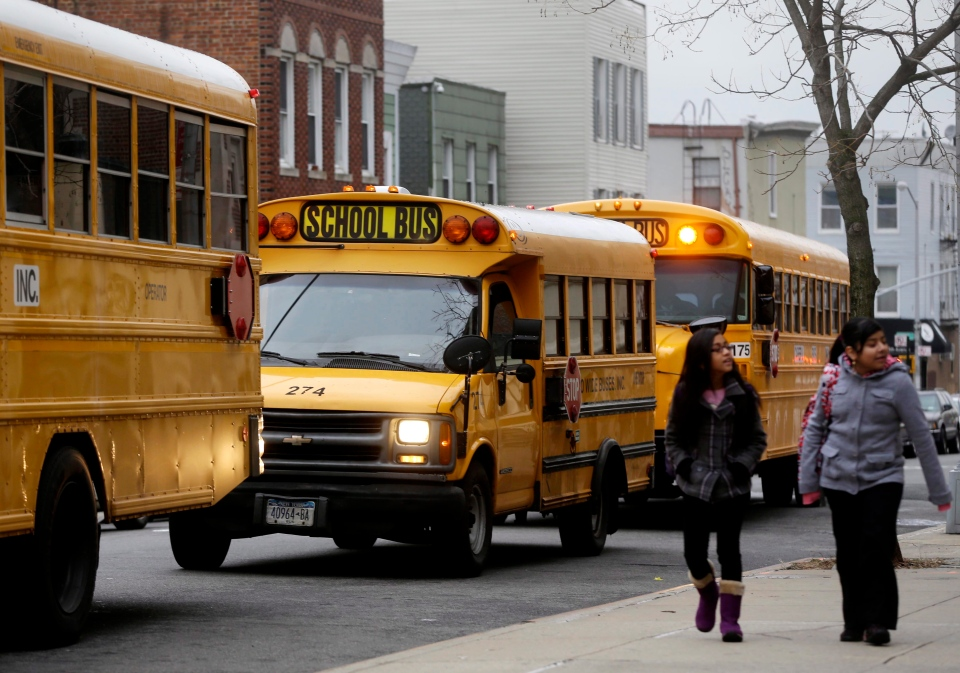 School buses line up to drop off students in New York, Tuesday, Jan. 15, 2013. A strike by New York City school bus drivers that had been threatened for weeks will start Wednesday morning, affecting 152,000 students, the president of the union representing the drivers announced Monday. (AP Photo/Seth Wenig)