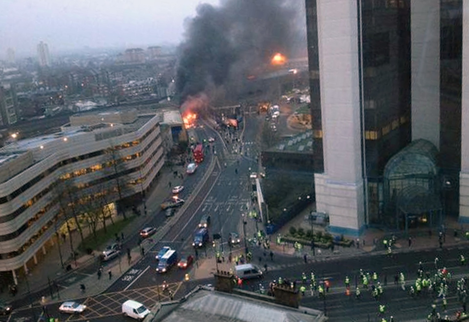 In this overhead view showing smoke and flames at the site of a helicopter crash in central London, as people gather to view the scene shortly after the incident, early Wednesday Jan. 16, 2013. (Victor Jimenez / PA)