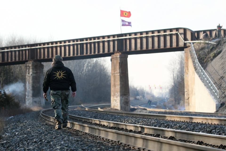 A Mohawk warrior crosses the CN and the CP train tracks crossing in Tyendinaga, Ont., on Tuesday, Jan. 16, 2013. (Lars Hagberg / THE CANADIAN PRESS)