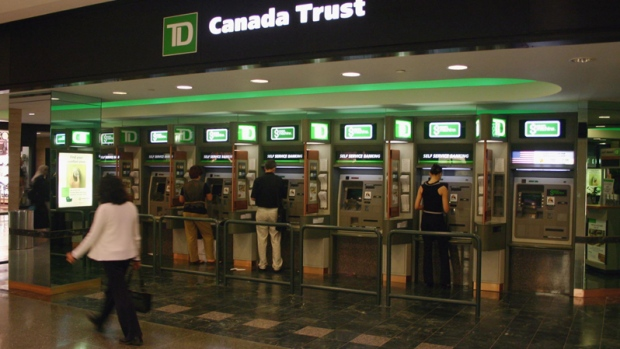 Customers use bank machines at the TD bank in Toronto. (THE CANADIAN PRESS)