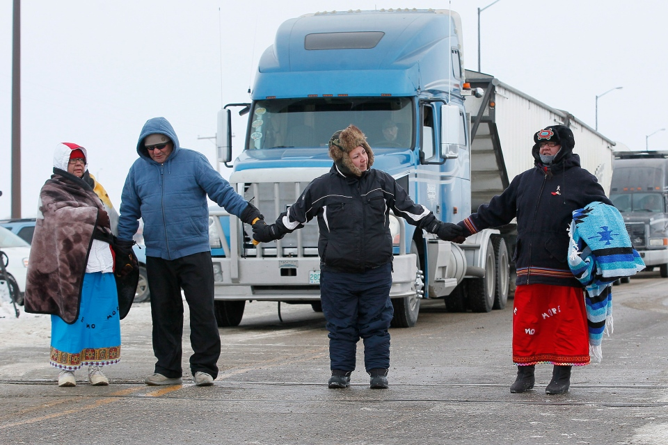 Four aboriginal protestors prepare to be arrested at a blockade of a CN railroad track just west of Portage La Prairie, Man., on Wednesday, January 16, 2016. (John Woods / THE CANADIAN PRESS)