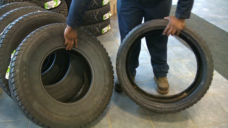 Brandon Hill with Kal-Tire shows the difference between tires with wide sidewalls, and tires without - Hill said thinner tires (such as the one on the right side) leave vehicles more susceptible to damage caused by driving over potholes.