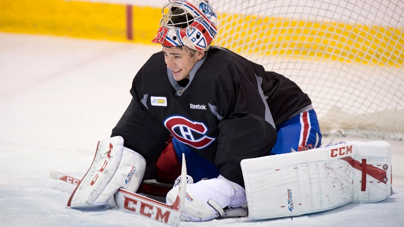 Montreal Canadiens goaltender Carey Price slips on his face mask during their training camp Tuesday, January 15, 2013 in Brossard, Que. THE CANADIAN PRESS/Paul Chiasson
