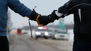 Four Idle No More demonstrators who were prepared to be arrested hold hands at a blockade of a CN railroad track just west of Portage La Prairie, Man., on Wednesday, Jan. 16, 2013. (John Woods / THE CANADIAN PRESS)