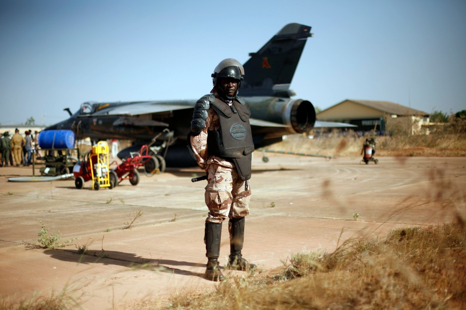 A Malian special forces soldier stands guard in front of a French Mirage fighter jet on the military side of Bamako's airport Wednesday Jan. 16, 2013. (AP / Jerome Delay)
