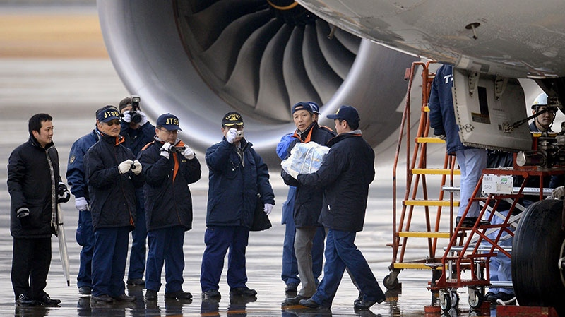 An official carries a main battery that was removed off an electrical room beneath the cockpit of an All Nippon Airways 787 at Takamatsu airport in Takamatsu, western Japan, Thursday, Jan. 17, 2013. (Kyodo News)