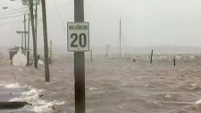 A sign peaks above flooding waters in Pointe-du-Chene, New Brunswick is seen in this undated photo.