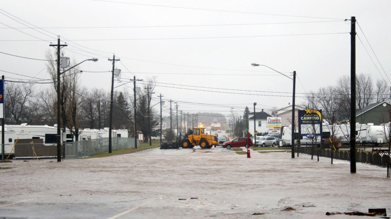 High water reaches Main St. as a plow blocks traffic in Shediac N.B. on Tuesday Dec. 21, 2010. (Peter Langis / THE CANADIAN PRESS)