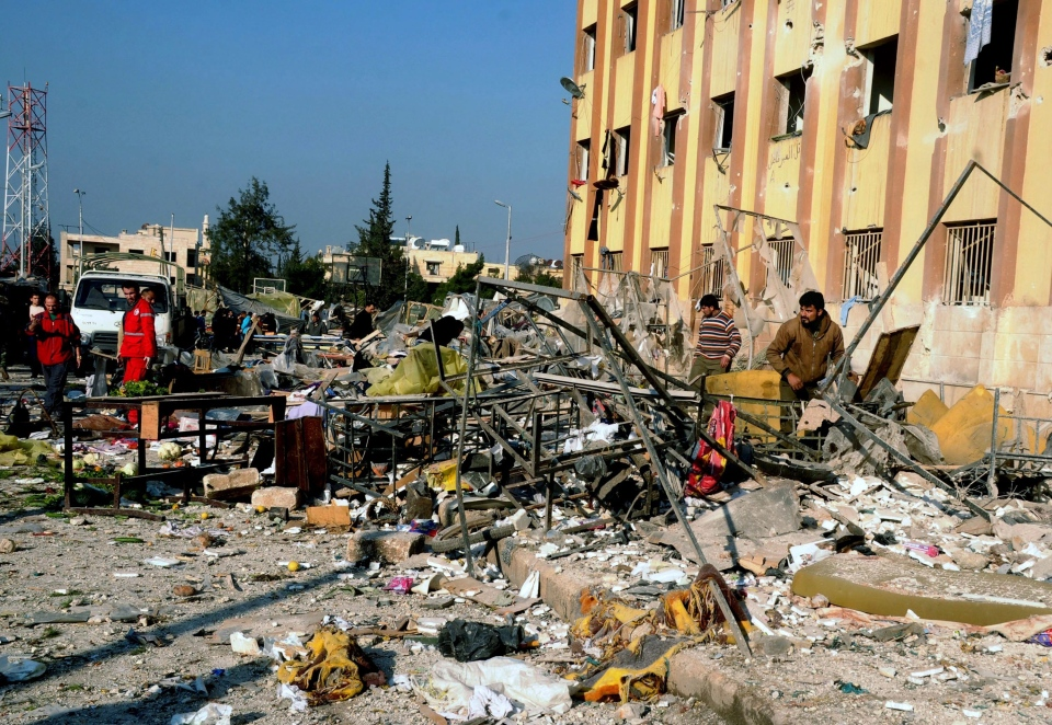 In this photo released by the Syrian official news agency SANA, Syrian people gather at the site after an explosion hit a university in Aleppo, Syria, Tuesday, Jan. 15, 2013. (AP Photo/SANA)