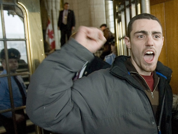 A protester chants as he is escorted out of the Parliament buildings in Ottawa Thursday, March 13, 2008. (Tom Hanson / THE CANADIAN PRESS)
