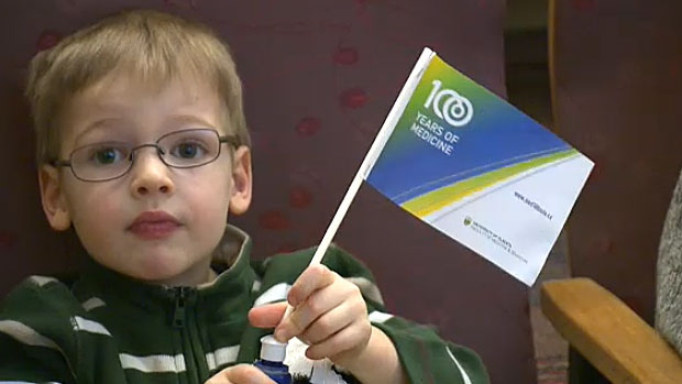 A young boy holds up a flag marking the centennial year for the University of Alberta's Faculty of Medicine and Dentistry.