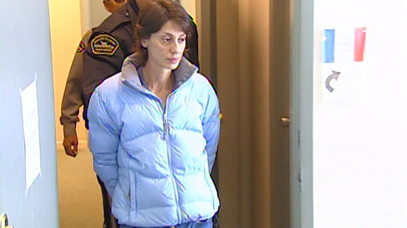 Nicole Ryan, who tried to hire a hit man to kill her husband, walks with two guards behind her in this undated image.