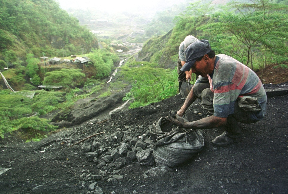 A man collects dirt and stones dug from a tunnel in Muzo, in the heart of Colombia's emerald-mining region, in this 2002 file photo. (AP Photo/Ricardo Mazalan)