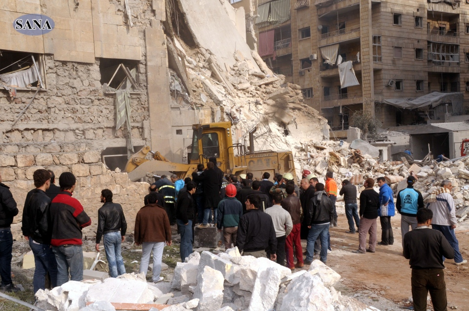 Rescue workers and bystanders at a building damaged by a rocket attack, that killed at least 12 people, in Aleppo, Syria, Friday, Jan. 18, 2013. (SANA)