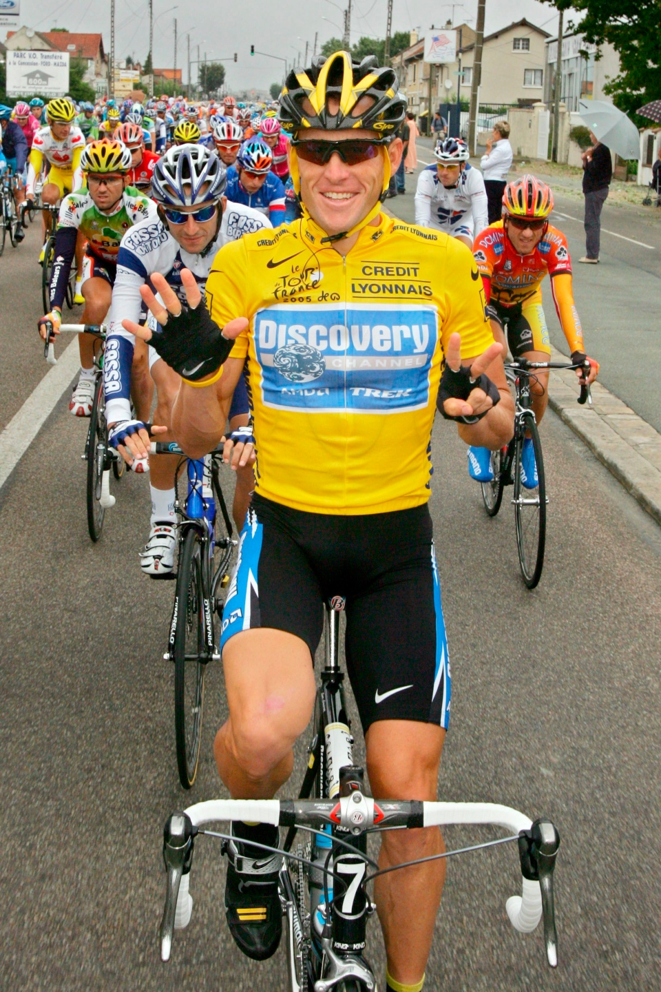 Lance Armstrong signals seven for his seventh straight win in the Tour de France cycling race as he pedals during the 21st and final stage of the race between Corbeil-Essonnes, south of Paris, in 2005. By admitting to Oprah Winfrey that he doped during his professional cycling career, Lance Armstrong potentially opened himself up to a stream of litigation that could hurt his pocketbook for years to come. (AP / Peter Dejong)