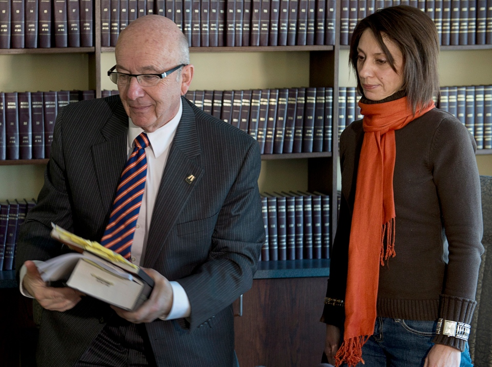 Nicole Ryan, the Nova Scotia woman who tried to hire a hit man to kill her abusive husband, follows her lawyer Joel Pink, left, from a news conference in Halifax on Thursday, Jan.17, 2013. (Andrew Vaughan / THE CANADIAN PRESS)
