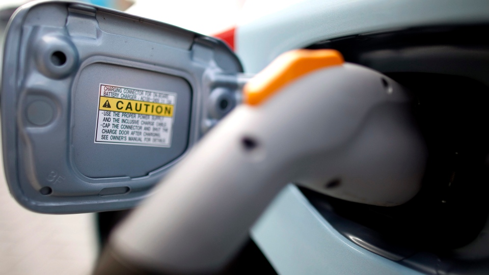 A power cable is seen attached to an electric vehicle in downtown Vancouver, B.C. Tuesday, Sept. 14, 2010. (THE CANADIAN PRESS / Jonathan Hayward)
