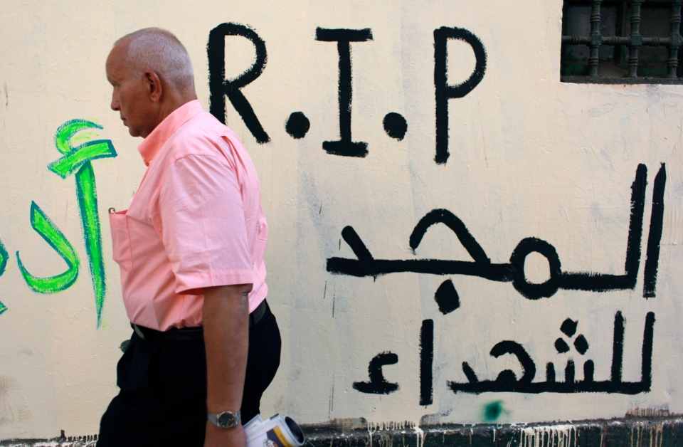 """An Egyptian man walks past newly painted graffiti that reads in Arabic """"glory for the martyrs,"""" on a wall that was whitewashed during a cleanup campaign to erase old murals, in Tahrir Square, Cairo, Egypt, Wednesday, Sept. 19, 2012. (AP / Nasser Nasser)"""