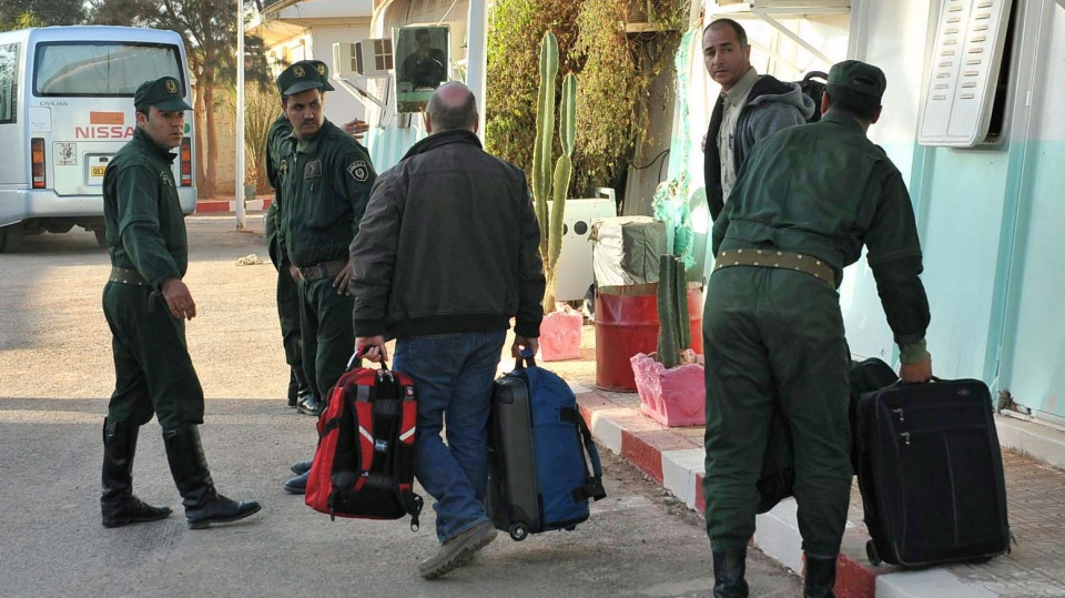 Two British hostages, Peter, right, and Alan, carrying his luggage, center, no family name available, gather their belongings after being released, in Ain Amenas, near the gas plant where they were kidnapped by Islamic militants, Saturday, Jan. 19, 2013. (AP / Anis Belghoul)