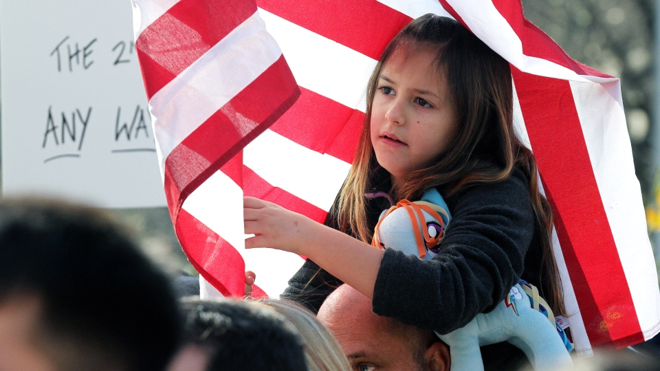 Nine-year-old Summer Stayton got wrapped up in a United States flag while sitting on her father Jason's shoulders during a Guns Across America rally on the Georgia State Capitol steps, Saturday Jan. 19, 2013 in Atlanta. (AP Photo / Atlanta Journal-Constitution, Phil Skinner)
