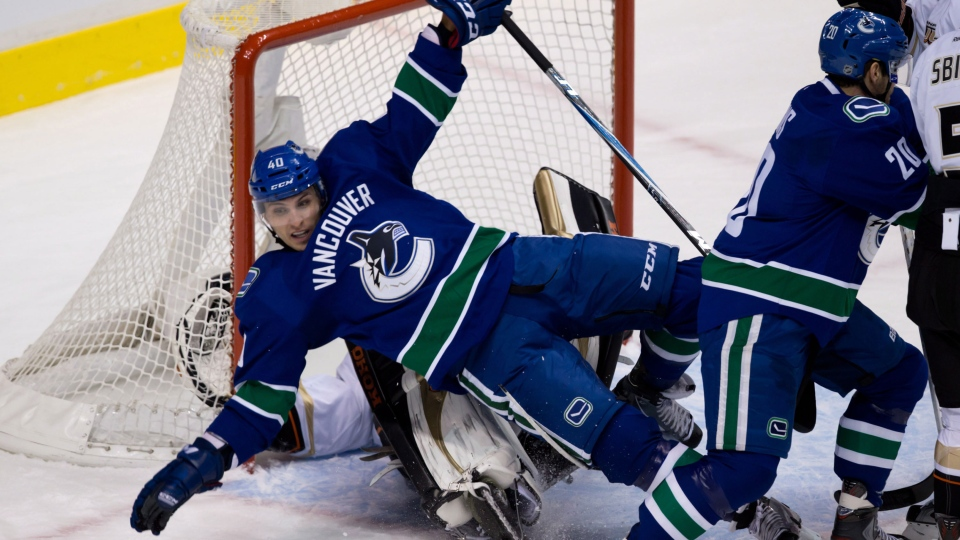 Vancouver Canucks' Maxim Lapierre, centre, is pushed into Anaheim Ducks' goalie Jonas Hiller, of Switzerland, during first period NHL hockey action in Vancouver on Saturday, January 19, 2013. (Darryl Dyck / THE CANADIAN PRESS)