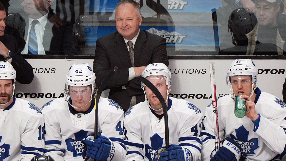 Toronto Maple Leafs head coach Randy Carlyle smiles from behind the bench during third period NHL hockey action against the Montreal Canadiens in Montreal, Saturday, January 19, 2013. (Graham Hughes / THE CANADIAN PRESS)