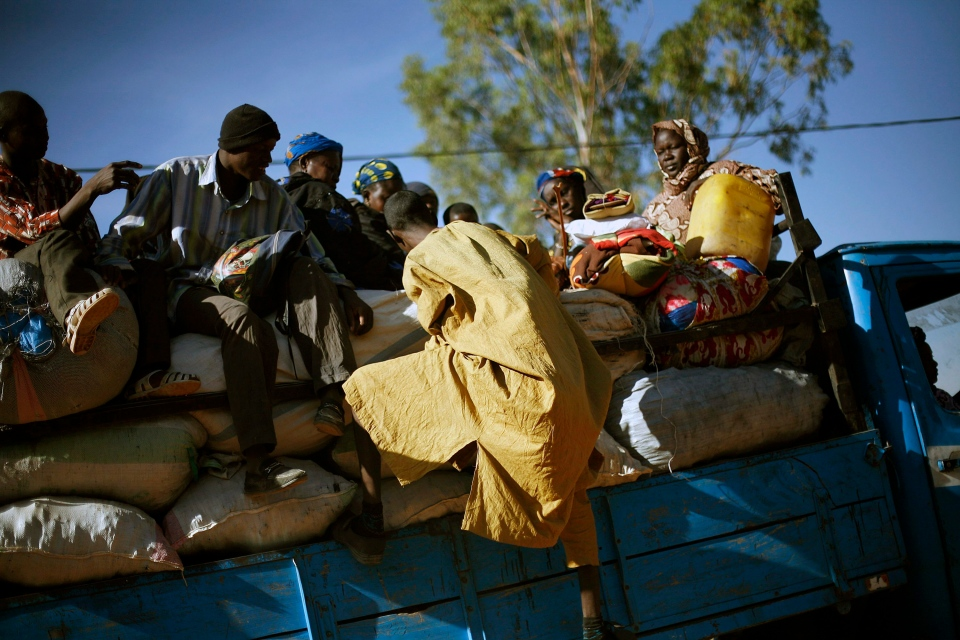 Travellers climb back on a transport truck after being checked by Malian soldiers at a checkpoint in Niono, Mali, some 400 km north of the capital Bamako Saturday Jan. 19, 2013. (AP / Jerome Delay)