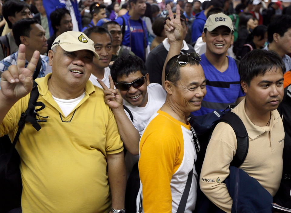 """Overseas Filipinos who were working at the sprawling oil field in Algeria which was attacked by terrorists, flash the """"V"""" sign as they queue up at the Philippine Immigration upon arrival at the Ninoy Aquino International Airport in Manila, Philippines, Sunday, Jan. 20, 2013. (AP / Bullit Marquez)"""