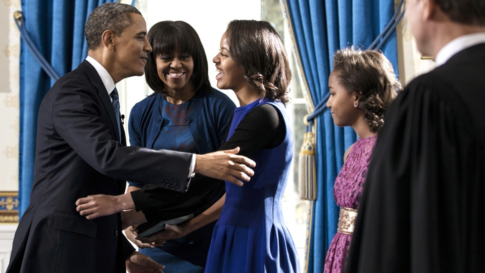 President Barack Obama embraces daughter Malia as first lady Michelle Obama and daughter Sasha, right, and Supreme Court Chief Justice John Roberts, Jr., look on after the official swearing-in in the Blue Room of the White House, Sunday, January 20, 2013 in Washington. (AP Photo / Brendan Smialowski, Pool)