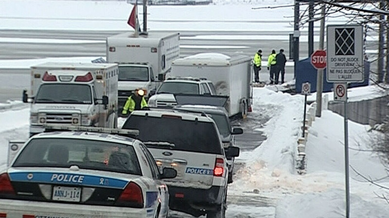 Police investigate the scene where a car was found submerged in the Ottawa River, Sunday, Jan. 20, 2013.