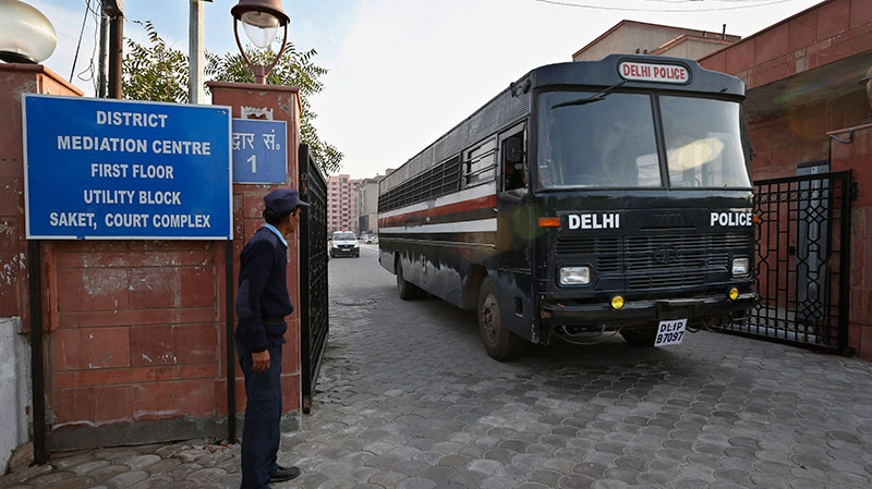 A Delhi police van, believed to be carrying the five men facing charges that they raped and murdered a 23-year-old woman aboard a moving bus in the capital last month, comes out of a district court in New Delhi, India, Monday, Jan. 21, 2013. (AP / Saurabh Das)