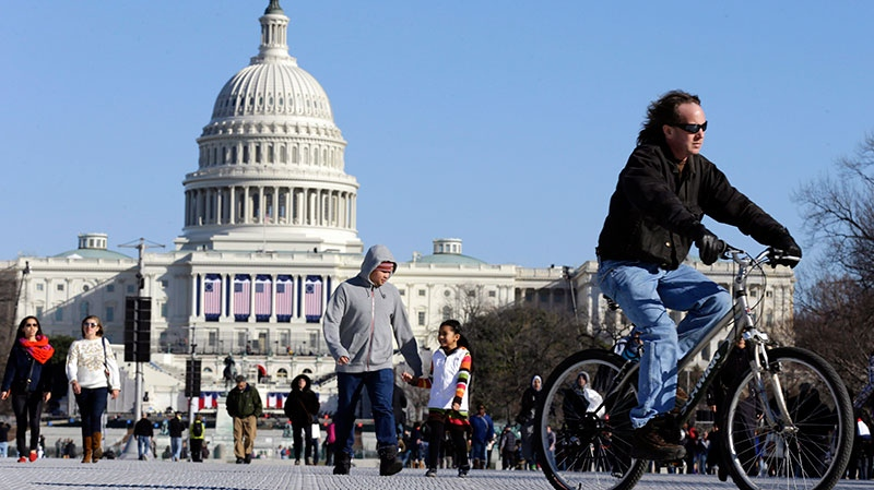 A man rides a bicycle as others walk on the National Mall Sunday, Jan. 20, 2013. (AP / Alex Brandon)