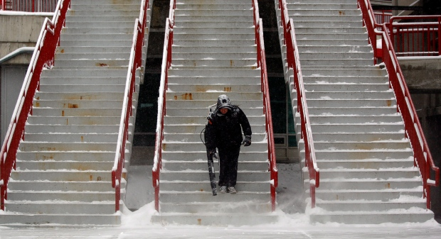 An employee of the Saddledome uses a leaf blower to clear snow from the steps of the arena as a light snow falls in Calgary, Alta., on Jan. 14, 2013. (Jeff McIntosh / THE CANADIAN PRESS)