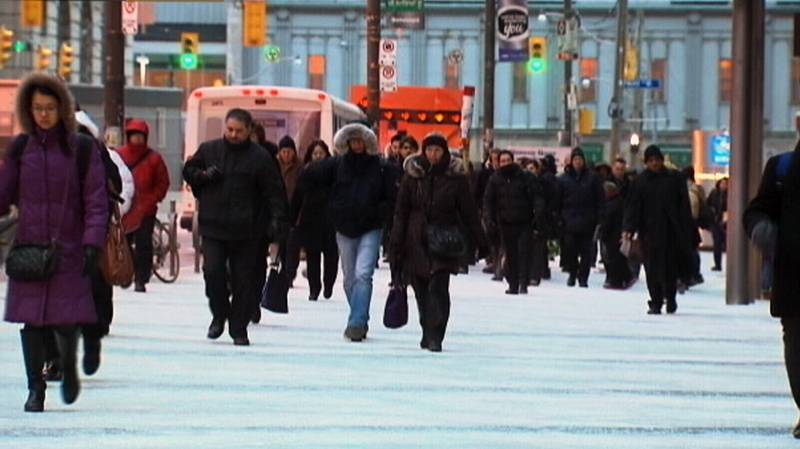 People bundle up as temperatures drop in Toronto on Jan. 21, 2013.