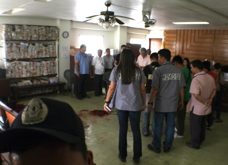 Philippine National Police investigators examine the courtroom at the Regional Trial Court building in Cebu city in central Philippines where a Canadian national identified as John H. Pope opened fire killing two people and wounding a prosecutor before being fatally shot by police Tuesday, Jan. 22, 2013. (AP / Chester Baldicantos)