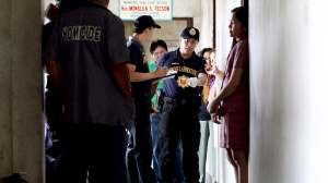 Scene of the Crime Operatives (SOCO) of the Philippine National Police examine the scene where prosecutor Maria Teresa Casino was wounded by Canadian national John H. Pope at the Regional Trial Court building in Cebu city in central Philippines Tuesday, Jan. 22, 2013. (AP / Chester Baldicantos)