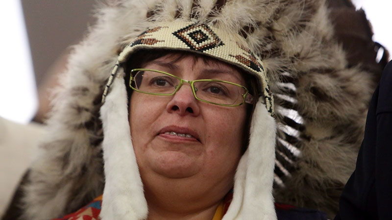 Attawapiskat Chief Theresa Spence, wearing a headdress, takes part in a drum ceremony before departing a Ottawa hotel to attend a ceremonial meeting at Rideau Hall with Gov. Gen. David Johnston in Ottawa, Friday Jan. 11, 2013. (Fred Chartrand / THE CANADIAN PRESS)