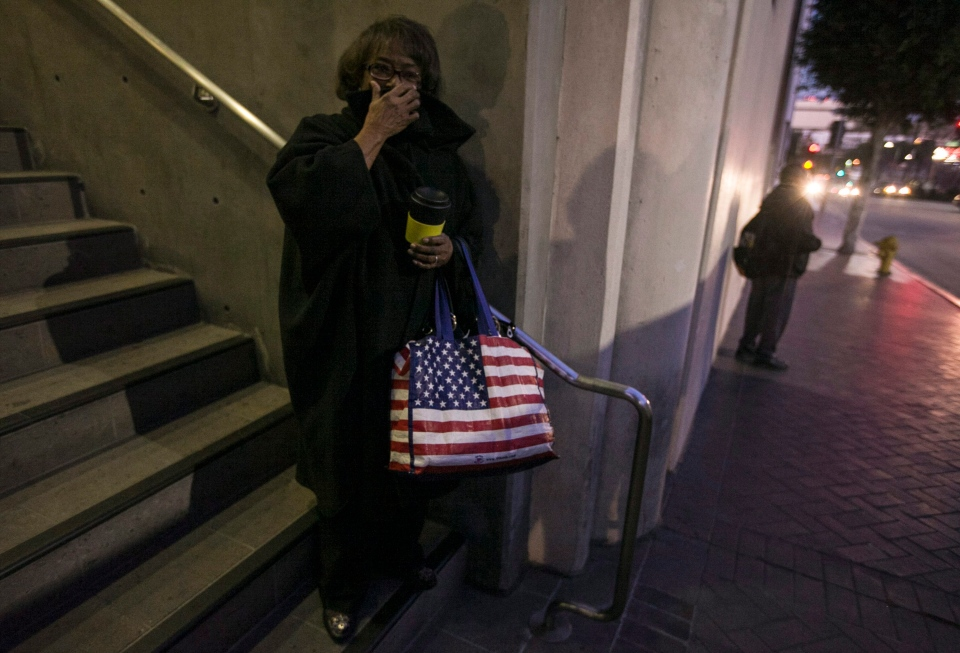 Doris Wooten covers up from the cold as she waits for a shuttle bus outside the Los Angeles Unified school headquarters in Los Angeles, Tuesday, Jan. 15, 2013. (AP / Damian Dovarganes)